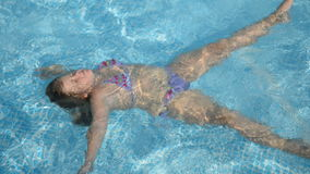 Little girl in the pool at home stock footage