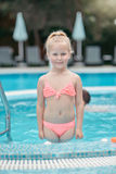 Little girl in the pool. Summer day in the pool little girl with white hair and a pink bathing suit stock photos