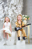 A little girl and pop musician with guitar sit on letters Stock Image