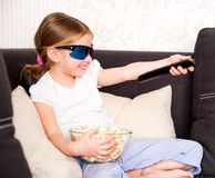 Little girl watching TV. Little girl with popcorn in 3D glasses holding a remote control Royalty Free Stock Photos