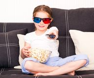 Little girl watching TV. Little girl with popcorn in 3D glasses holding a remote control watching TV Stock Image