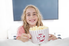 Little girl with popcorn in from of tv. A little girl with popcorn in from of tv Royalty Free Stock Photo