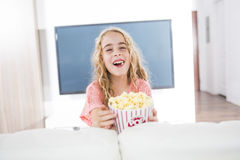 Little girl with popcorn in from of tv. A little girl with popcorn in from of tv Stock Photo