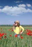 Little girl with poppy flower. Spring season Stock Photography