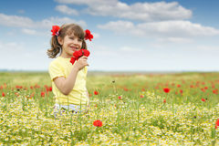 Little girl with poppy flowers on meadow Royalty Free Stock Images