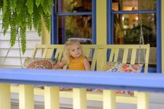 Little girl on a porch swing on a summer day stock photos