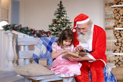 Grandfather playing Santa Claus role for granddaughter. royalty free stock image