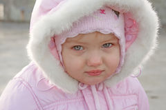 Little girl portrait close up outdoor. Portrait of a little girl in a pink colored winter coat with fur hood on Stock Image