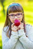 Little girl portrait eating red apple in garden. Royalty Free Stock Photo