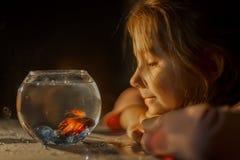 Little girl portrait with fish in round aquarium