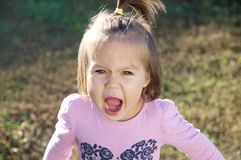 Little girl portrait outdoor screaming grasping defending her opinion royalty free stock photo