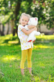 Little girl portrait in a park - holding toy bear. Outdoor Stock Images