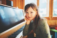 Little girl portrait. Little girl playing piano at home Royalty Free Stock Image