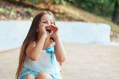Little girl portrait, sits and shouts putting her hands to her mouth, natural lighting outdoors. In summer stock photos