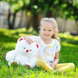 Little girl portrait with a toy in a park Stock Photo