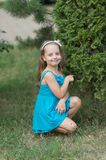 Little girl pose at green bush on grass, beauty. Happy child smile in summer park, childhood. Kid fashion, beauty, look, hair, hairstyle Royalty Free Stock Photos