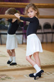 Little girl poses at ballet barre. Reflection in mirror Royalty Free Stock Image