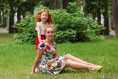 Little girl poses with her mother in summer park, shallo Stock Images