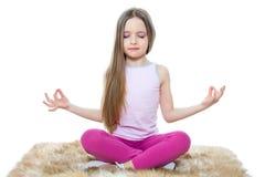 Little girl posing. Cute little girl meditating isolated on white Royalty Free Stock Image