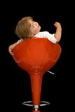 Little girl posing. Little girl playing and having fun posing on a red swivel chair - isolated on black royalty free stock images