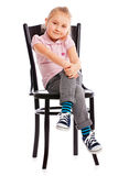 Little girl posing on antique chair Stock Photos