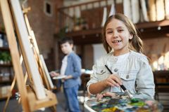Little Girl Posing in Art Class. Waist up portrait of cute little girl painting picture on easel in art class and holding palette, copy space royalty free stock photography