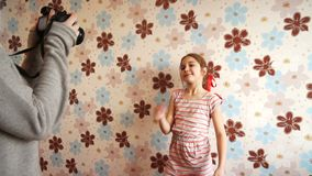 Little girl posing in front of the camera. A little girl posing in front of the camera against the wall with flowers stock video footage