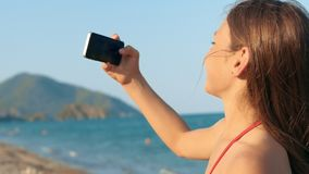 Little girl posing in front of phone camera making selfie at seashore stock footage