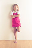 Little girl posing in front of a wall Royalty Free Stock Photography