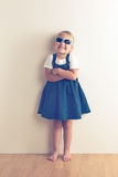 Little girl posing in front of a wall Stock Photo