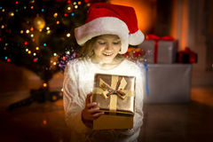 Little girl posing with glowing golden gift box Stock Images