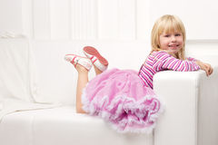 Little girl posing happily on sofa Royalty Free Stock Photos