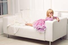 Little girl posing happily on sofa Royalty Free Stock Image