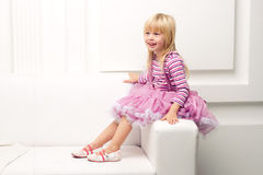 Little girl posing happily on sofa Stock Photos