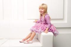 Little girl posing happily on sofa Stock Photos