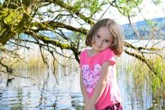 Little girl posing on a lake Stock Photos
