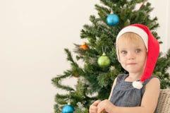 Little girl posing near the christmas tree Royalty Free Stock Photos