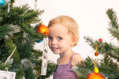 Little girl posing near the christmas tree Royalty Free Stock Photography