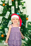 Little girl posing near the christmas tree decorated with dollar Stock Images