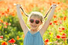 Little girl posing in a poppies Stock Images