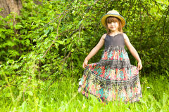 Little girl posing in a straw hat in the park Royalty Free Stock Images