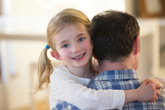 Little girl posing whilst being carried by her father Stock Images