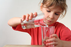 Little girl pour out water from one glass to other. Little girl in red shirt pour out water from one glass to other, half body Royalty Free Stock Photos
