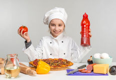 Little girl pour pizza with ketchup Royalty Free Stock Photography