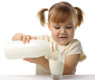 Little girl pouring milk in glass Royalty Free Stock Photos