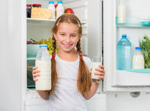 Little girl pouring milk in glass Stock Photo