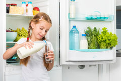 Little girl pouring milk in glass Stock Images