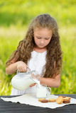 Little girl pouring milk in glass outdoor summer. Little girl pouring milk in glass outdoor. Curly kid having breakfast. Summer time Royalty Free Stock Images