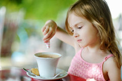 Little girl pouring sugar into hot chocolate Stock Image