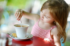 Little girl pouring sugar into hot chocolate Stock Images